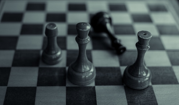 Chess game black king is checkmated and fallen on chessboard game over