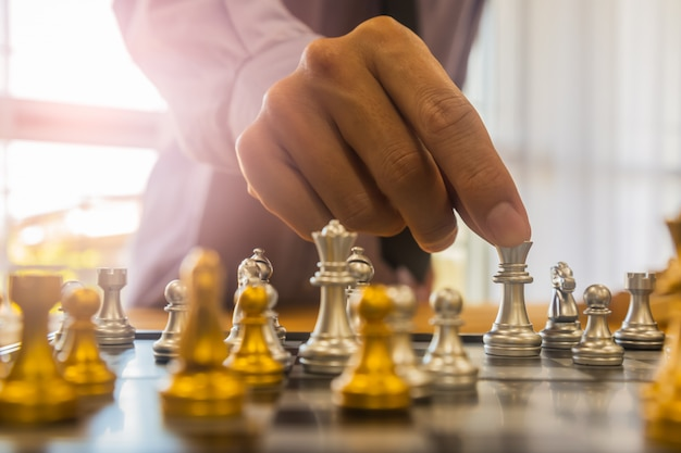 Chess game on chess board behind business man background. business concept to present financial information and marketing strategy analysis.