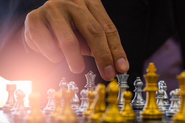 Chess game on chess board behind business man background.