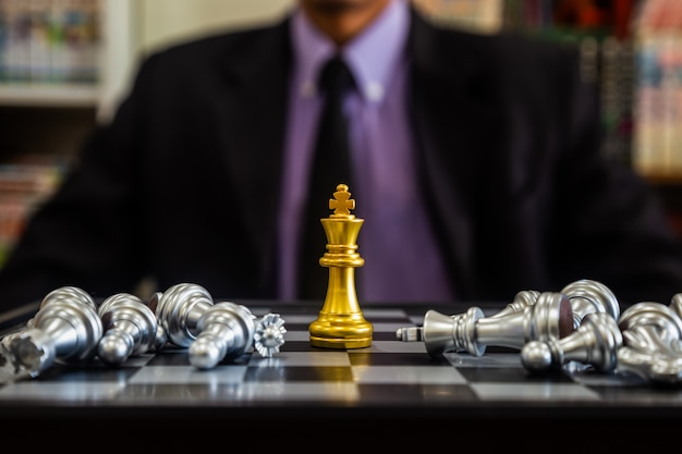 Chess game on chess board with businessman