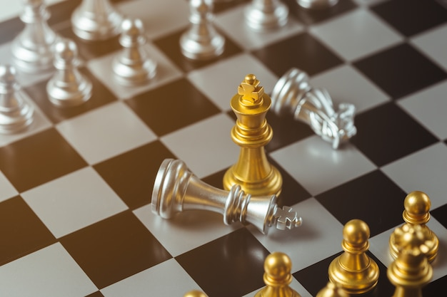 Chess game gold king standing and silver chessboard, business strategy concept.
