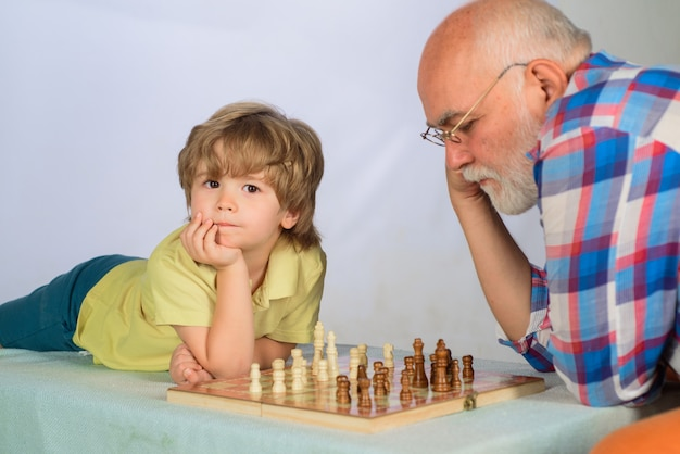 Chess game grandfather and grandson playing board game together family relationship with grandpa and