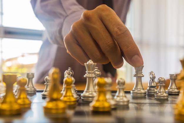 ビジネスの男の背景の背後にあるチェス盤のチェスゲーム。財務情報とマーケティング戦略分析を提示するビジネスコンセプト。