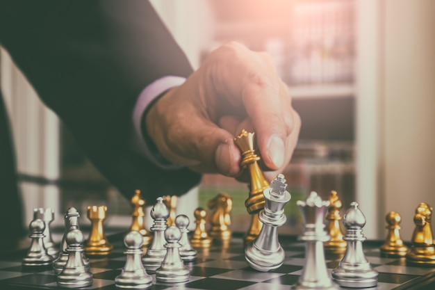 ビジネスマンの背景の背後にあるチェス盤のチェスゲーム