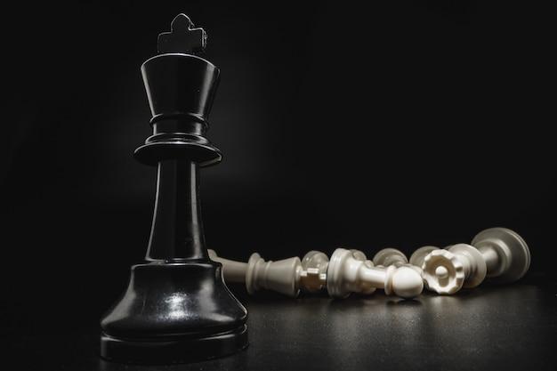 Шахматная игра с шахматными фигурами на черном фоне крупным планом