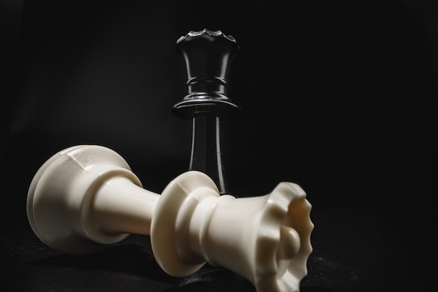 Chess game with chess pieces against black background close up