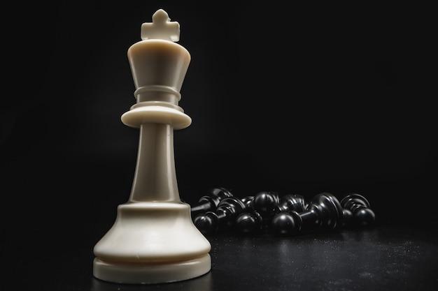 Шахматная игра с шахматными фигурами на черном фоне