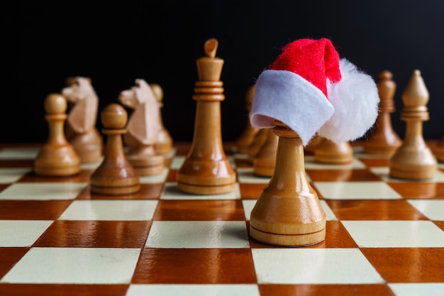 Chess game with figures in the christmas cap of the tournament