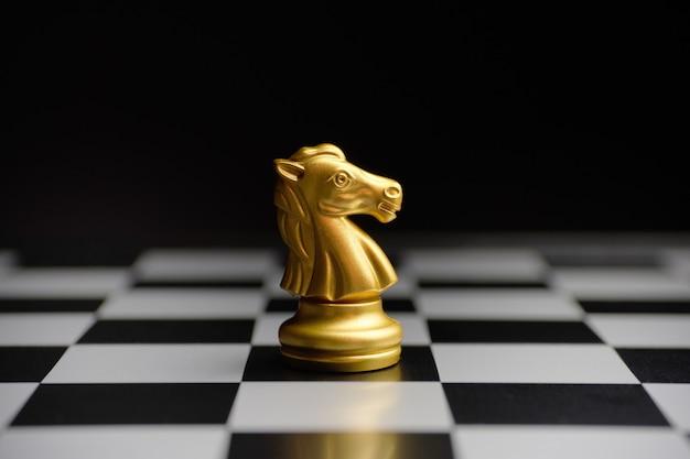 Шахматная позолоченная фигура лошади на доске.