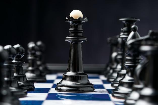 Chess king among his black pieces