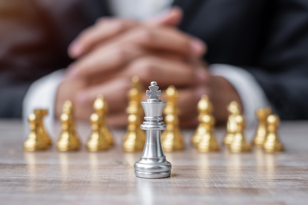 Chess king figure against chessboard opponent with businessman manager background.