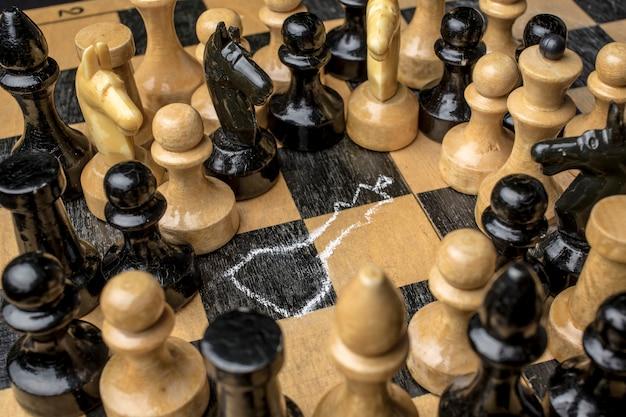 Шахматный король силуэт нарисован на шахматной доске с шахматными фигурами вокруг него