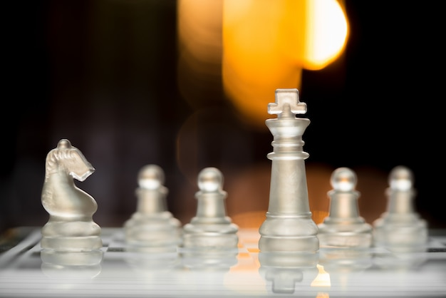 Chess king staying before the set of another with bokeh light background.