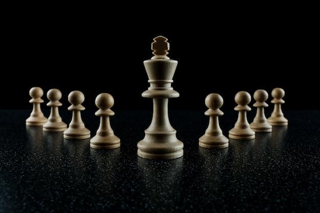 Шахматный король со свитой пешек на черном фоне