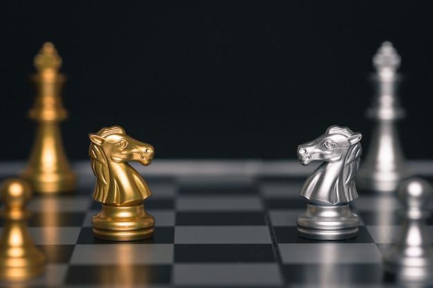 銀と金の馬のチェスはチェスのゲームで向かい合っています
