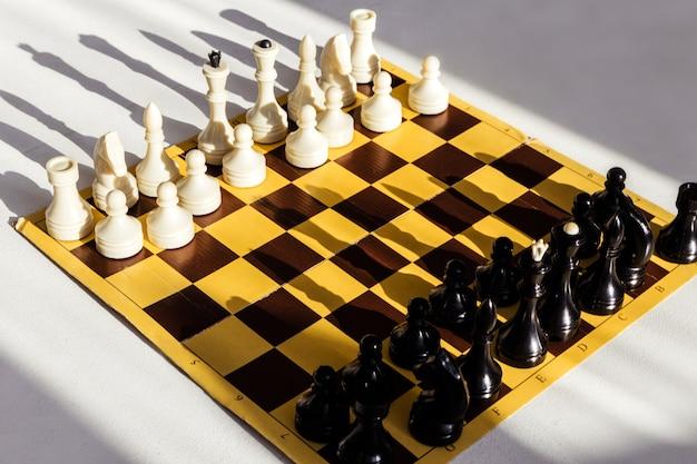 Шахматы на светлой поверхности стола в помещении интеллектуальные игры для детей и взрослых логическое мышление че ...