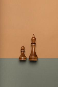 平らな背景の上面図にチェスのポーンと王