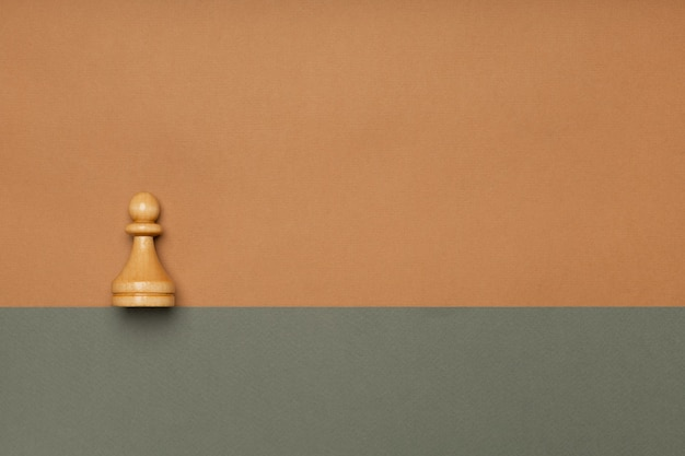 Chess pawn on flat background top view