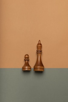 Chess pawn and king on flat background top view