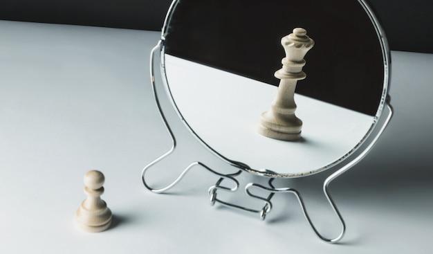 Шахматная пешка смотрит в зеркало
