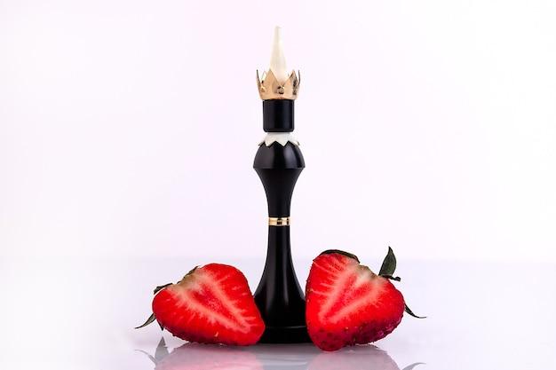 白い背景の上のイチゴの2つの半分を持つチェスの駒の王。愛と選択の概念。