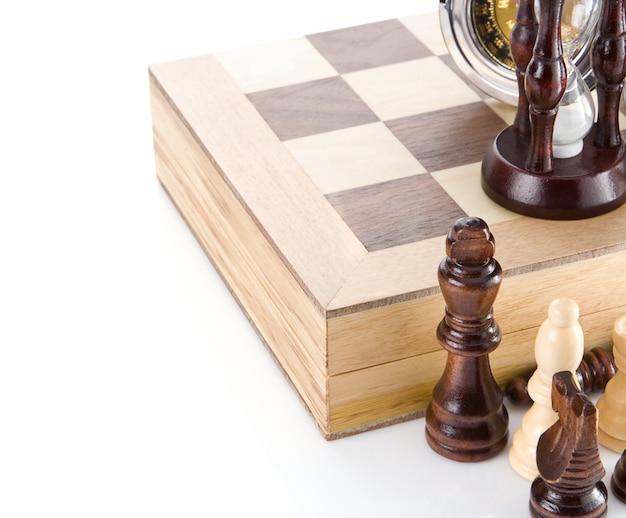 白い表面で隔離されたボード上のチェスの駒、時計、砂時計