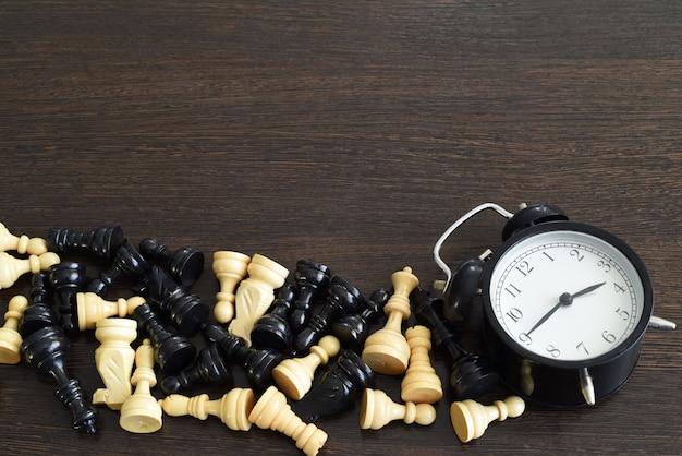 Шахматные фигуры и будильник на деревянных фоне