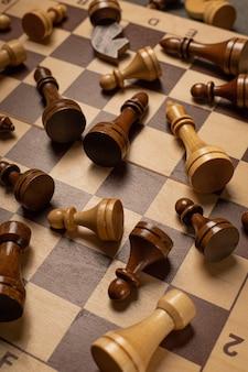 チェスの駒がチェス盤に無秩序に散らばっている
