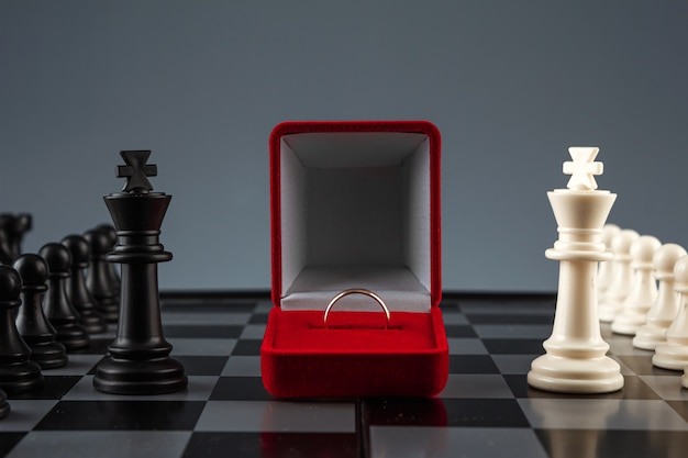 Chess pieces on a chessboard and a box with a golden ring