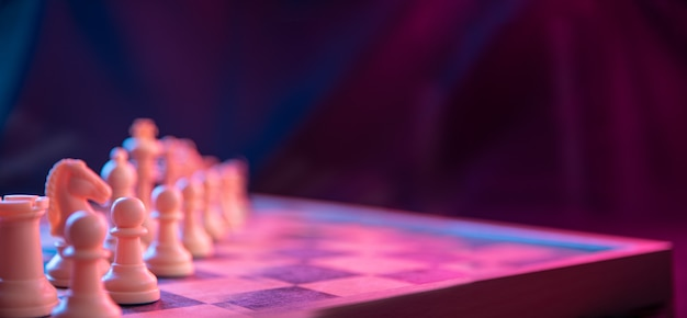 Chess pieces on a chessboard on a dark background shot in neon pink-blue colors. the figure of a chess .close up.