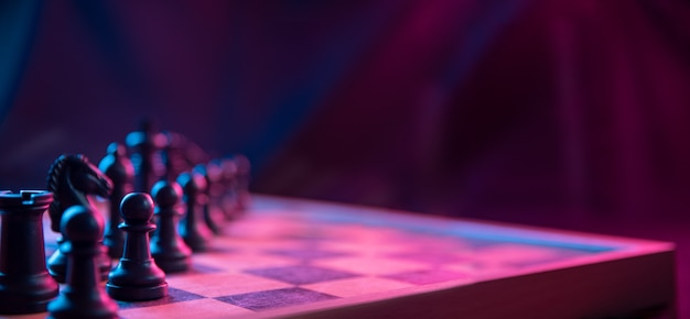 Chess pieces on a chessboard on a dark background shot in neon pink-blue colors.