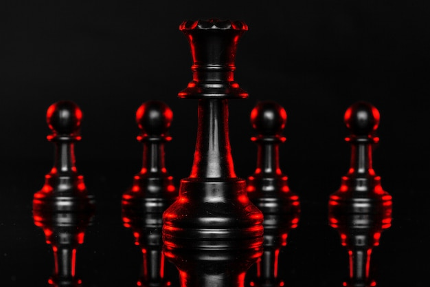 Chess pieces on dark background with red backlight