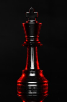 Chess pieces on dark with red backlight close up