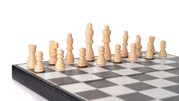 Chess pieces on game board against white background