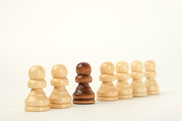 Шахматные фигуры в ряд. черная фигура выделяется на фоне остальных
