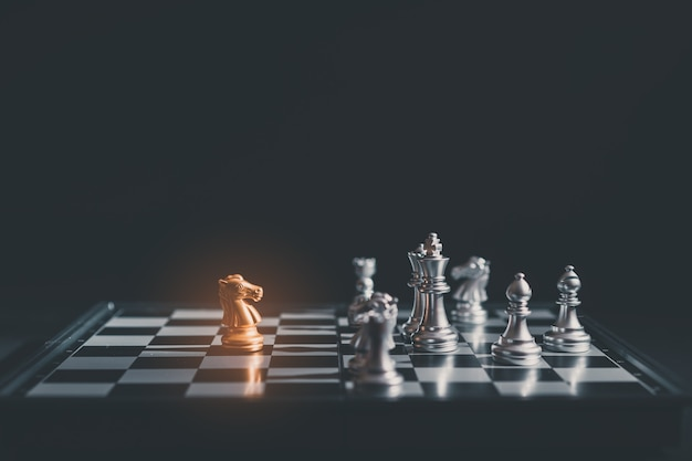 Chess pieces knights facing each other on chessboard.