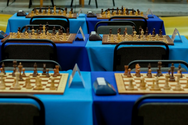 Chess pieces lined up across many boards in readiness for a big tournament