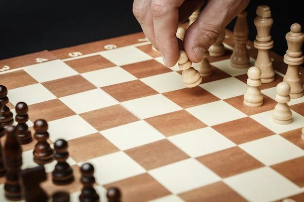 Шахматные фигуры на шахматной доске у темной стены. рука делает первый шаг, концепция стратегии успеха и правильный выбор