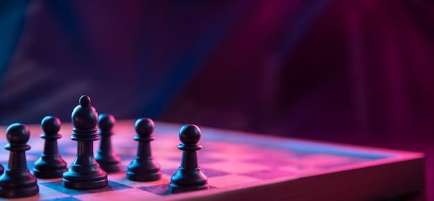 Шахматные фигуры на шахматной доске на темном фоне снятые в неоновых розово-голубых тонах. фигура в шахматы. крупным планом.