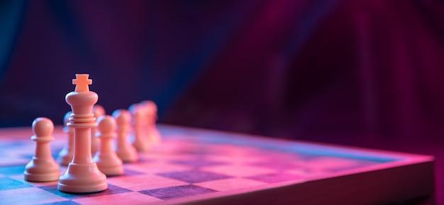 ネオンピンクブルーの色で撮影された暗い表面のチェス盤のチェスの駒。クローズアップ。