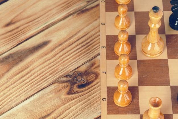 暗い背景に対して木製のチェス盤のチェスの駒