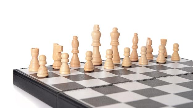 Шахматные фигуры на игровой доске на белом фоне