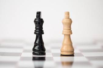 Chess pieces standing at the chessboard beside each other