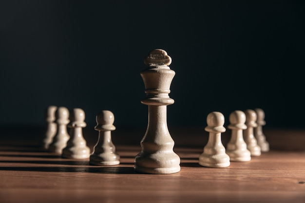 Chess pieces on the table on a dark wall