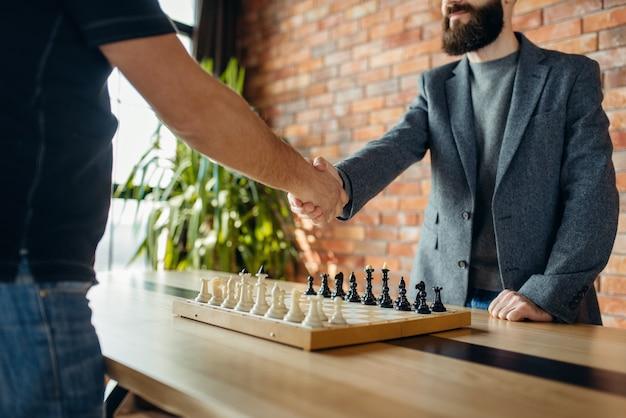 Шахматисты пожимают друг другу руки перед игрой