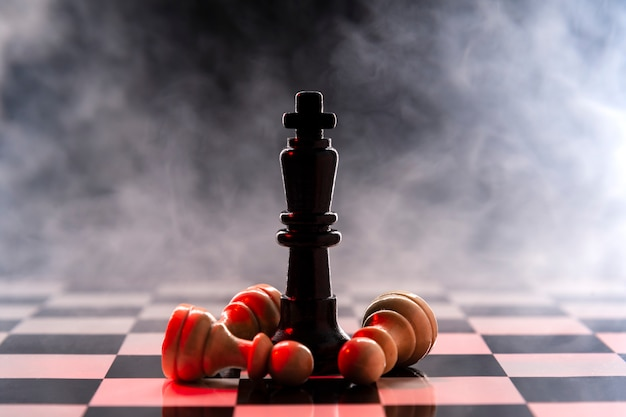 Chess queen defeats a batch of white pawns on a chessboard on a background with smoke