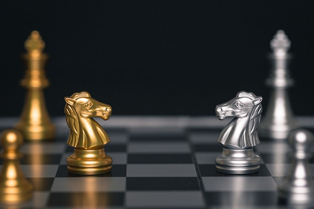 Chess of silver and gold horses face each other in a chess game