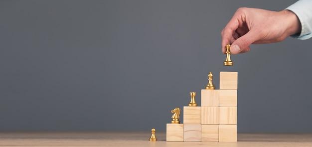 Шахматы, стоящие на пирамиде из деревянного строительного блока
