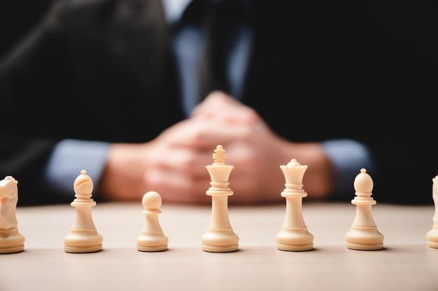 Шахматная стратегия для бизнес-лидерства и концепция успеха команды, соревнование лидера игры с командным вызовом силы, пешечная фигура на доске, победный интеллект шахматной доски