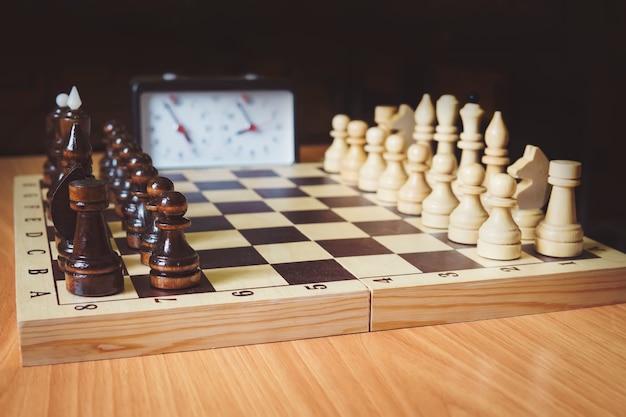 チェス盤、チェスの駒、チェス時計のクローズアップ。写真には、王、女王、ルークがいます。チェスゲームの始まり。最初の動き